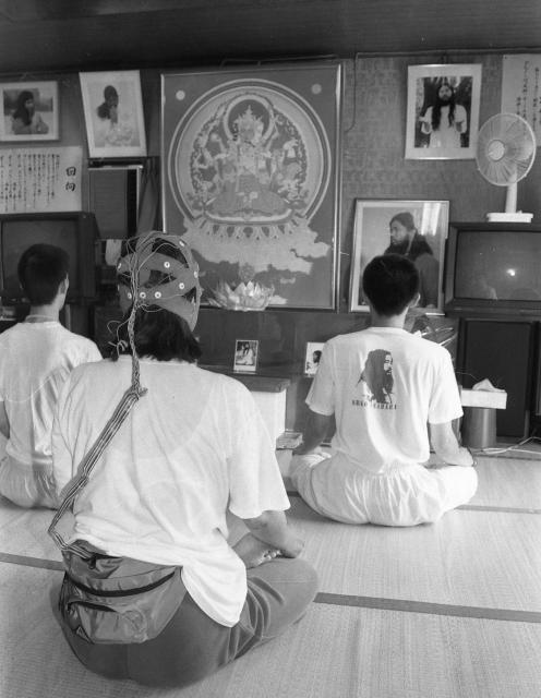 オウム真理教船橋支部で蓮華座を組んで瞑想する信徒たち。手前の人がつけているヘッドギアについて教団は、中に電極があり、教団代表だった松本死刑囚の発するテレパシーと同調することで修行の効果が上がると説明していた=1995年8月、千葉県船橋市