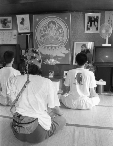 支部で蓮華座を組み瞑想する信徒たち。手前の人がつけたヘッドギアについて教団は、中に電極があり、教団代表だった松本死刑囚のテレパシーと同調することで修行の効果が上がると説明していた=1995年8月