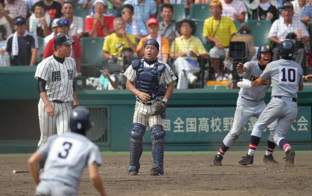 9回表仙台育英2死満塁、日野の中飛が敵失を誘い、三塁走者庄子(右から2人目)、二塁走者田中(10)が生還。逆転を許し投手白根と捕手出射はぼうぜんとする=2010年8月11日