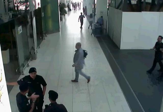 襲撃の2分前、空港の出発ホールに入る正男氏(中央)=関係者提供
