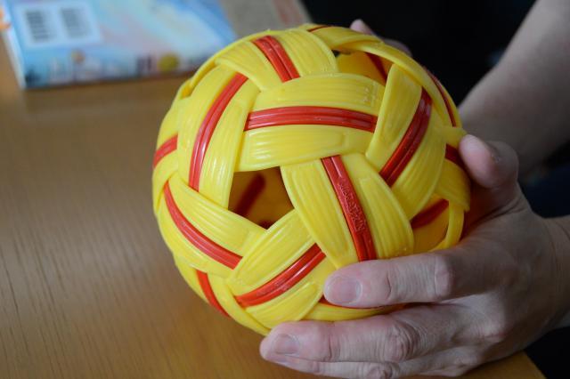 セパタクローの公式球を見つめる虹山さん。「私が心をひかれたのは、セパタクローのボールが閉じていないところ。何も詰まっていない、風通しのいいボールです」