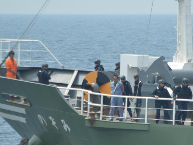 容疑船役の貨物船での船舶検査訓練の様子。立入検査隊の隊員らが、容疑船の航海士(中央の青い服)の立ち会いで貨物検査を進める。左では所持品検査で作業用ナイフが見つかった機関長を見張っている=7月25日午前、房総半島沖
