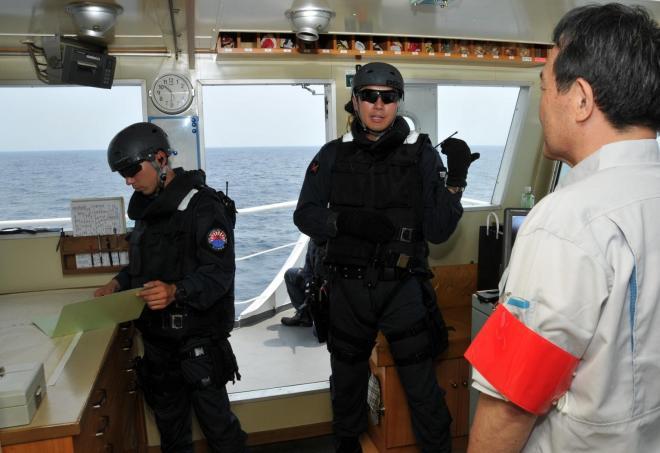 船舶検査訓練で容疑船に乗り込み、船長とやり取りする「立入検査隊」の隊員ら=7月25日午前、房総半島沖