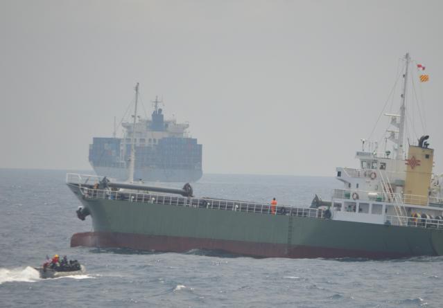 米国側に次いで韓国側も訓練。米海軍のボートに韓国沿岸警備隊が乗って船舶検査に向かった。訓練とは関係ない巨大な貨物船の姿も=7月25日午前、房総半島沖