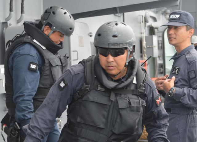 船舶検査訓練を終えて戻った立入検査隊の隊員ら。指導役の上官(右)と話す=7月25日午前、房総半島沖の海自護衛艦「むらさめ」艦上