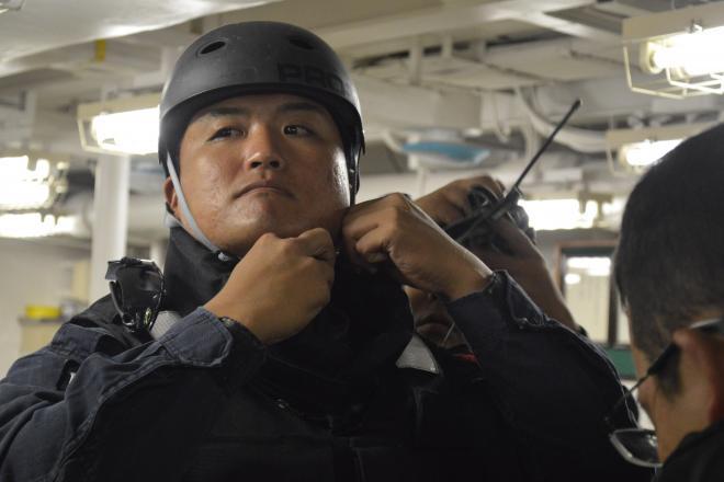 船舶検査訓練に備え、互いに協力して装備をまとう海上自衛隊「立入検査隊」の隊員ら=7月25日午前、房総半島沖の護衛艦「むらさめ」艦内、藤田直央撮影