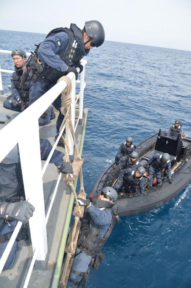 船舶検査訓練で容疑船役の貨物船に縄ばしごで乗り込む立入検査隊の隊員ら=7月25日午前、房総半島沖
