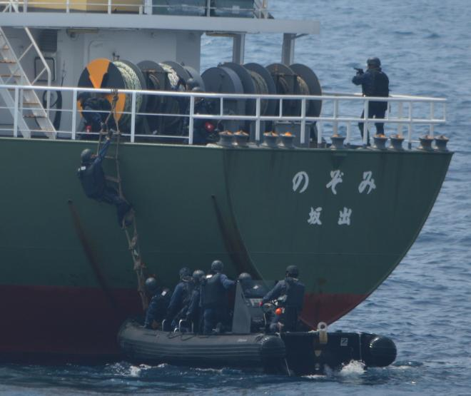 船舶検査訓練で容疑船役の貨物船に縄ばしごで乗り込む立入検査隊の隊員ら。右上では先に乗船した隊員が銃を構えている=7月25日午前、房総半島沖