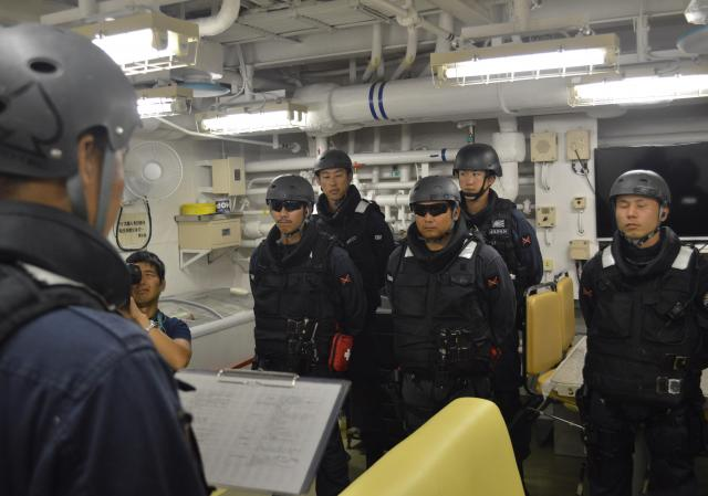 船舶検査訓練が始まり、立入検査隊が集合。隊長(左)が現状と任務、抵抗を受けた場合の武器使用について説明する=7月25日午前、浦賀水道を南進中の海自護衛艦「むらさめ」艦内