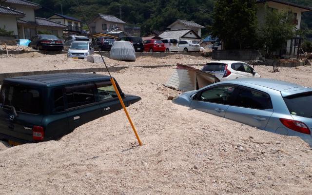 土石流で埋まった駐車場に放置された車