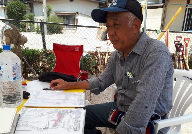 小屋浦4丁目第1町内会長の灘さん。安否確認と被害状況を1軒ずつして住宅地図を色分けしているが「先が見えない」