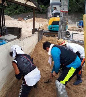 重機が入れない路地の土砂を撤去するボランティア