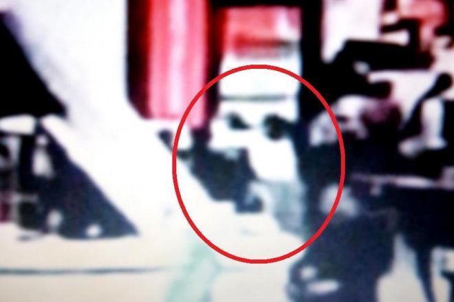金正男氏の背後から、白い長袖シャツを着た女が飛びついた瞬間の映像=関係者提供