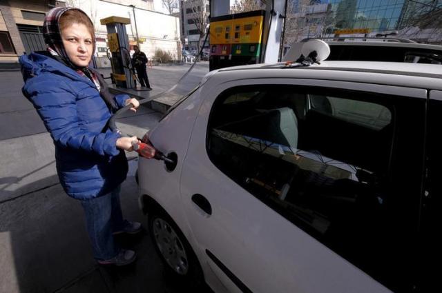 自分の車に給油するテヘランの女性=ロイター