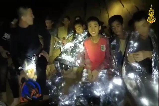 洞窟内でタイ海軍特殊部隊員と話す少年たち。発見されてからも酸素濃度が下がるなど危機的状況は続いた