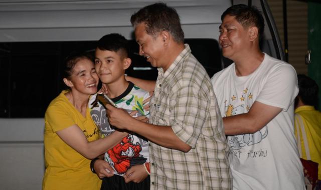 無事家に帰った少年に抱きついて喜ぶ家族。タイ政府から「取材は控えめに」といわれており、帰宅後、各メディアはインタビューなどは自粛した=タイ北部チェンライ郊外、7月18日