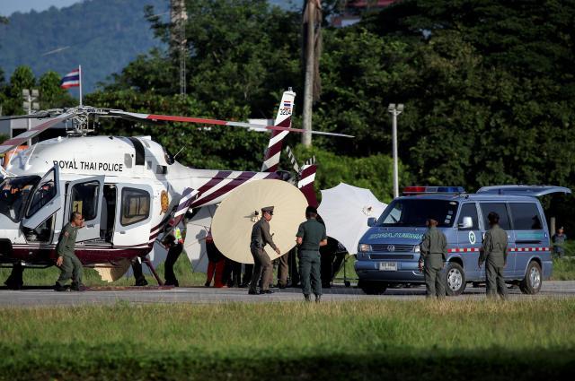 洞窟から救出された少年らを救急車からヘリコプターに移すタイ国軍関係者ら。少年らは報道陣に写されないため、がっちりガードされていた=7月9日、タイ北部チェンライ郊外