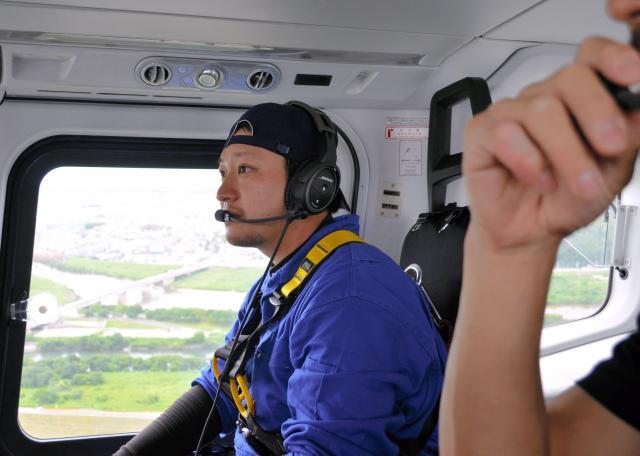 朝日新聞社ヘリ「あかつき」の機内でボール投下を待つ飯野祐平整備士