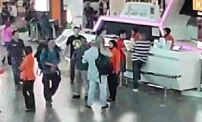 事件直後、空港職員に被害相談する正男氏(中央)の映像=関係者提供