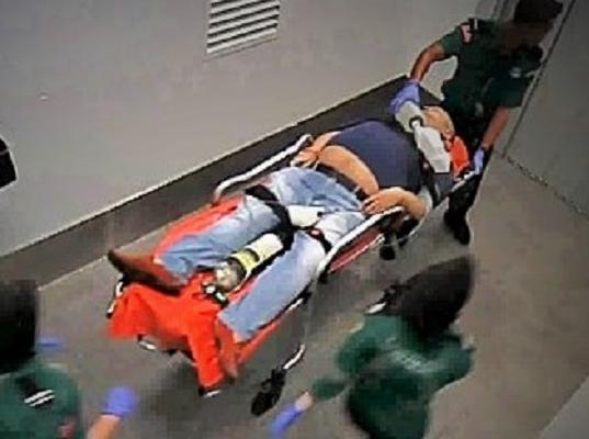 空港の診療所から運び出される正男氏(中央)の映像。股の間に酸素ボンベやモニターがある=関係者提供