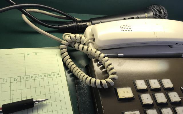公式記録員の席には、ボタンと電話とマイクが置かれている。ペンとスコアブックは必需品