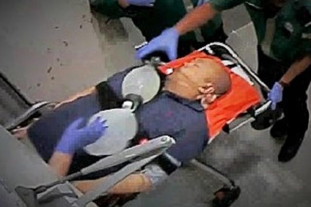 診療所で救命処置を受けた後、病院へ運び出される正男氏(中央)の映像=関係者提供