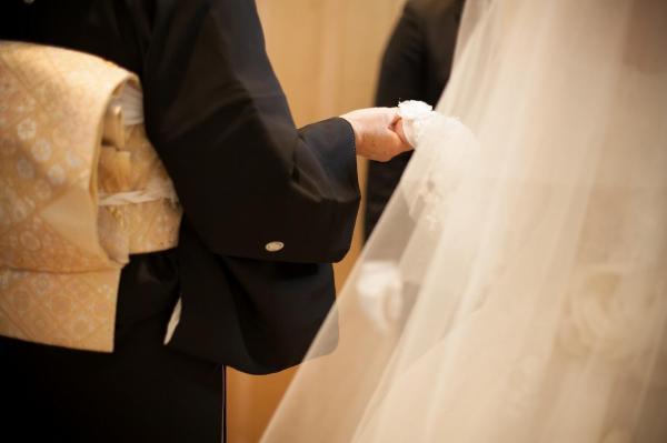 結婚式でドレス姿のかにこさんと手をつなぐ母