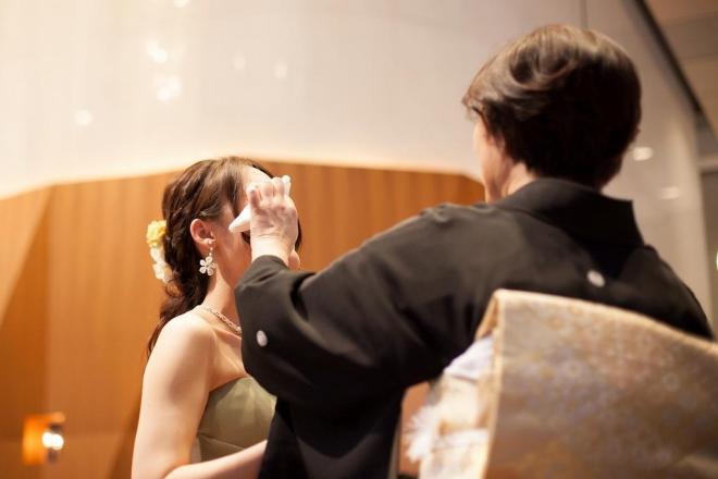 かにこさん(左)の結婚式で、娘の涙をぬぐう母