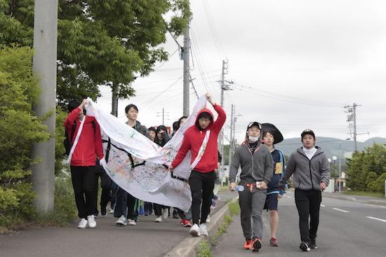 毎年恒例の名物行事、強歩遠足。全校生徒や教師らが30、50、70キロのどれかのコースを歩く。励ましてもらったり、誰かと一緒に歩いたり。最後は自分の足でゴールまで歩く様子は、「まさに人生と一緒」(田中さん)=北星学園余市高校提供