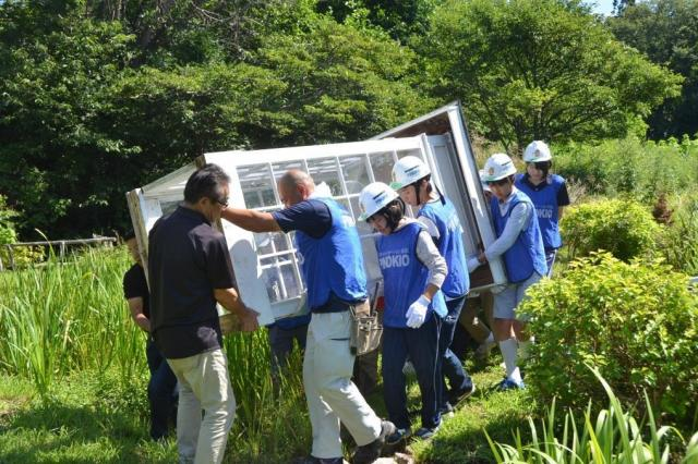 古い「風の電話ボックス」を撤去する中高生ら。これは庭の別の場所でオブジェとして飾られる