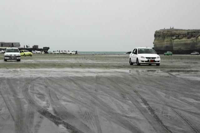 ゲシュム島とラーズ島の間の砂浜を走る自動車