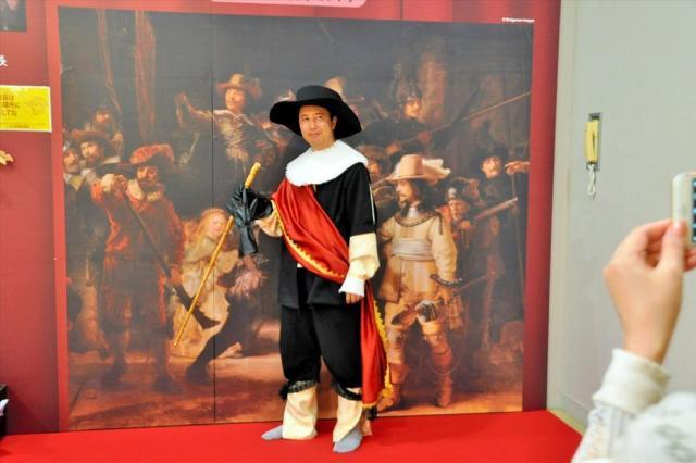 レンブラントの「夜警」のコック隊長のコスプレをする男性。赤いたすきや帽子、ステッキも用意してあり、ポーズをすれば臨場感あふれる名画になれる=徳島県鳴門市