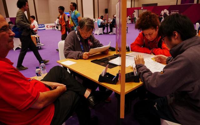 ゲーム前に暗号表の最終確認をする中尾共栄さん(左から2人目)とパートナーの瀬下拓未さん(右端)=8月21日、ジャカルタ