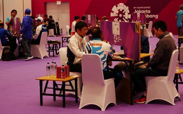 競技会場ではテーブルが離して置かれ、一斉にゲームをスタートさせます=8月21日、ジャカルタ