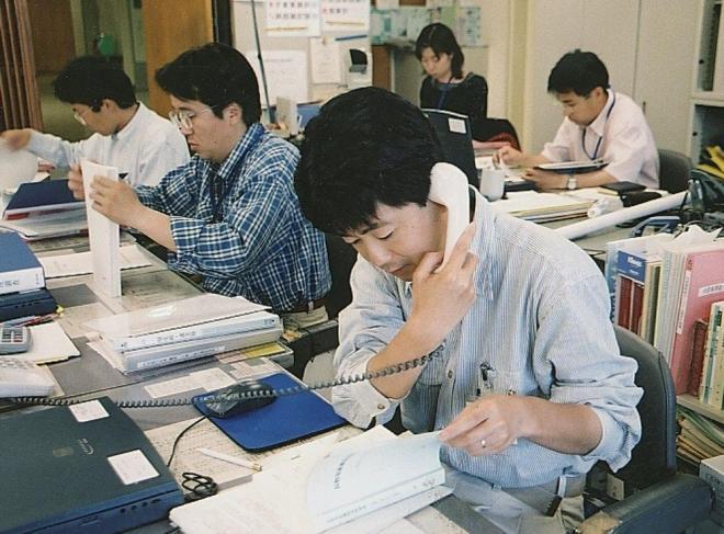 ネクタイの無いカジュアルな服装で仕事をする長野県職員=2002年6月5日