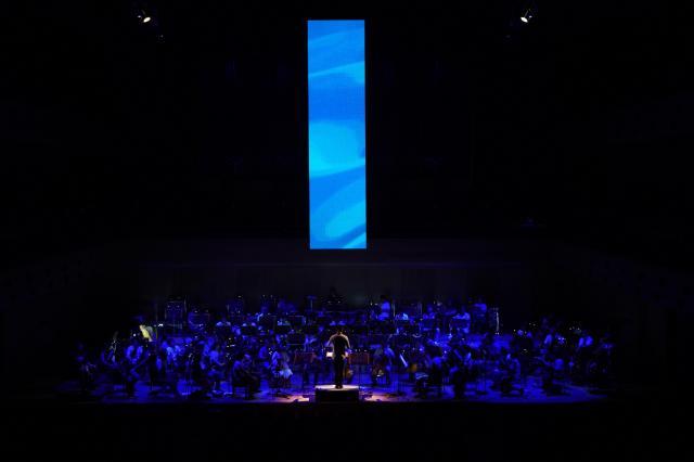縦長のスクリーンには指揮者の動きに合わせた映像が映し出される=写真提供・日本フィルⒸ山口敦