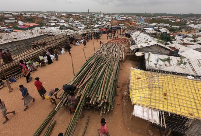 難民キャンプ内では、長い竹を運ぶ人々の姿が多く見られた。雨期の雨で流されないように簡易住居の補強をするための資材だ=2018年8月、バングラデシュ南東部・コックスバザール