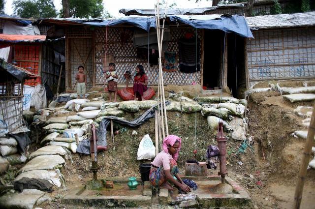 キャンプ内で洗濯するロヒンギャ難民。水は多くが土を掘ってくみ出しているが、十分な深さがなく、汚水と混ざってしまう場合もあるという=2018年8月、バングラデシュ南東部・コックスバザール
