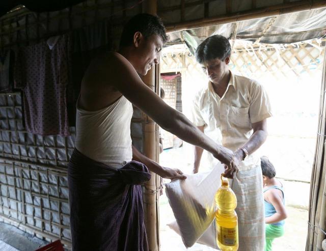 国際機関からの配給品を「業者」に売る、ラシッド・ウラーさん(左)。「もらったものを売るのは申し訳ないが、生活のため」と話した=2018年8月、バングラデシュ南東部・コックスバザール