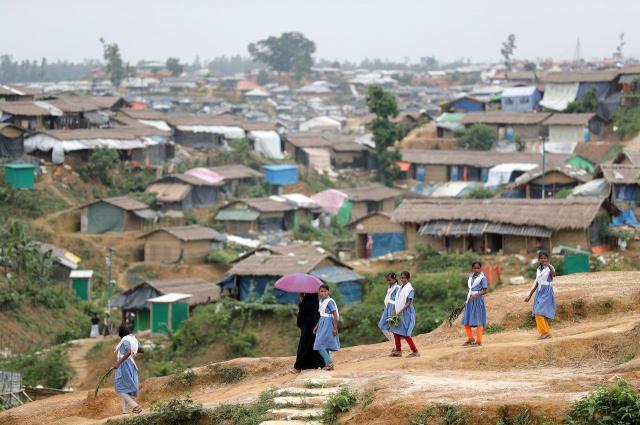 キャンプの中にある教育施設に向かう子どもたち。キャンプ内には簡易住居が肩を寄せ合うようにぎっしりとたちならんでいる=2018年8月、バングラデシュ南東部・コックスバザール