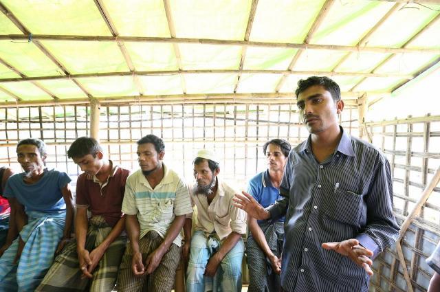 同じ地域の難民の会議で話す、ラシッド・ウラーさん(右)。教師だったことなどから、他の難民からまとめやくに選出され、会議では進行役をする=2018年8月、バングラデシュ南東部・コックスバザール