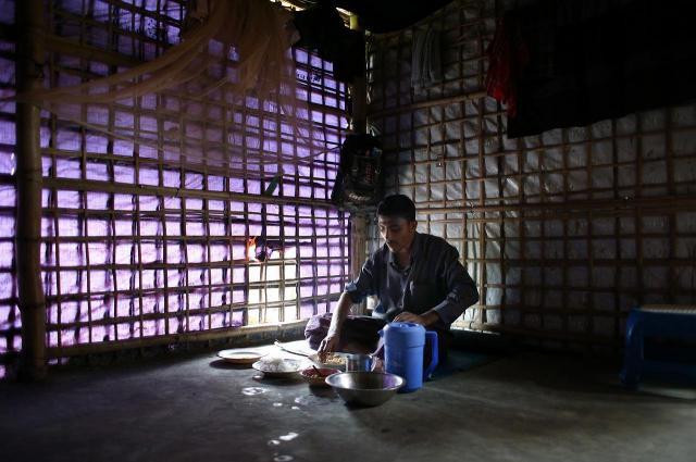 朝、1人で朝食を食べるラシッド・ウラーさん。竹を組んだ住居の中に電灯はない。くりぬいた「窓」からの光を頼りに食べ物を口に運んでいた=2018年8月、バングラデシュ南東部・コックスバザール