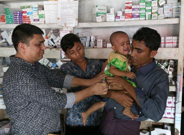 薬局で長女のロハネスちゃんにビタミン注射を打ってもらうラシッド・ウラーさん(右)。「娘には、とにかく健康に育ってほしい」と話した=2018年8月、バングラデシュ南東部、コックスバザール