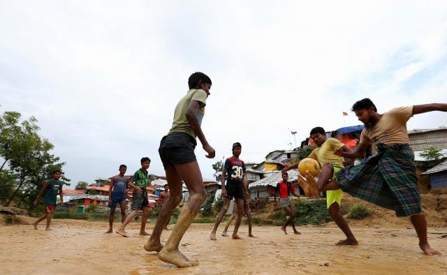 キャンプの中でサッカーをするロヒンギャ難民の子どもたち。空き地につくった「グラウンド」にはあちこちに水たまりがあり、すぐに泥だらけになっていた=2018年8月、バングラデシュ南東部・コックスバザール
