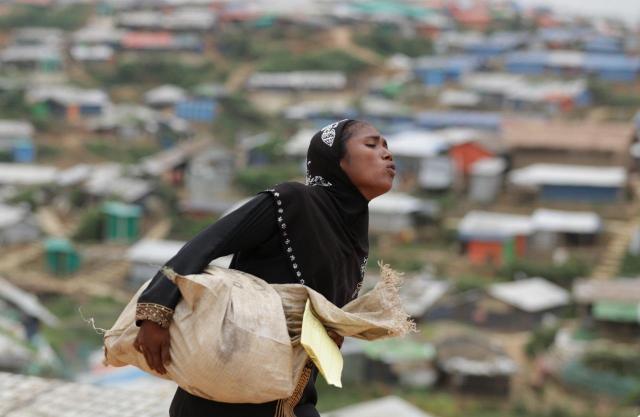 ロヒンギャ難民は、配給の食料を自分たちで運ぶ。小さい子どもや女性も重そうな米や油を自分の住居まで運び込んでいた=2018年8月、バングラデシュ南東部・コックスバザール