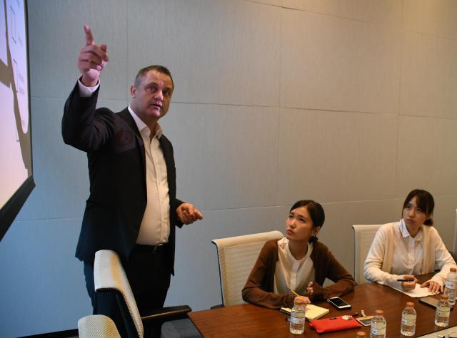 東洋大の学生に講義するジェレミー・ウォーカーさん(左)=8月30日、マカオ、益満雄一郎撮影