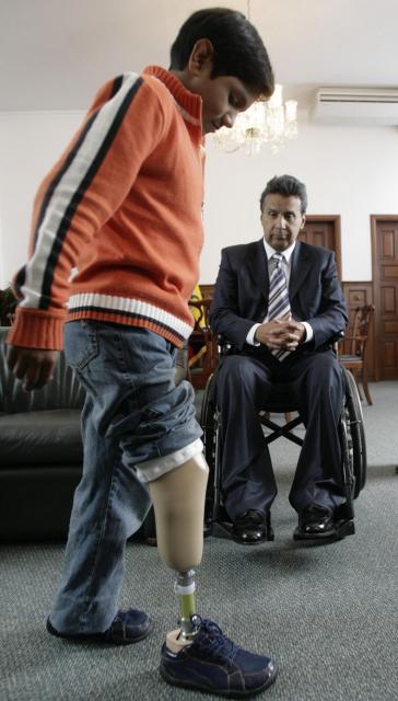 エクアドルの首都キトで2008年2月、義足を付けた少年を見守るモレノ副大統領(当時)=ロイター