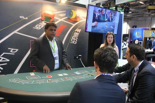 世界のカジノ産業の展示会「アジア国際娯楽展」で説明する出展企業の男性(左)=5月15日、マカオ、益満雄一郎撮影
