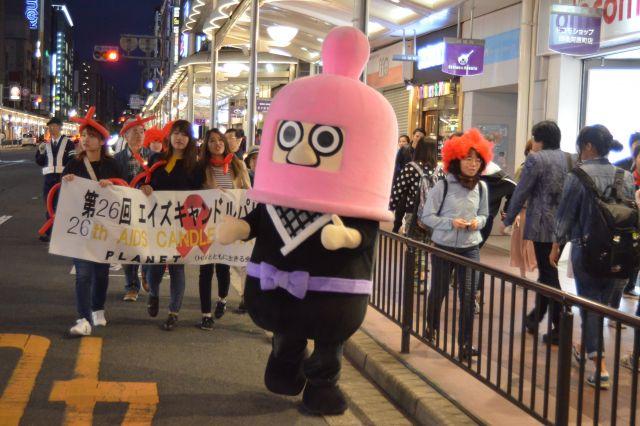 コンドームをイメージしたゆるキャラも登場し、道行く人に予防や検査の大切さを訴えたエイズキャンドルパレード=2018年5月、京都市
