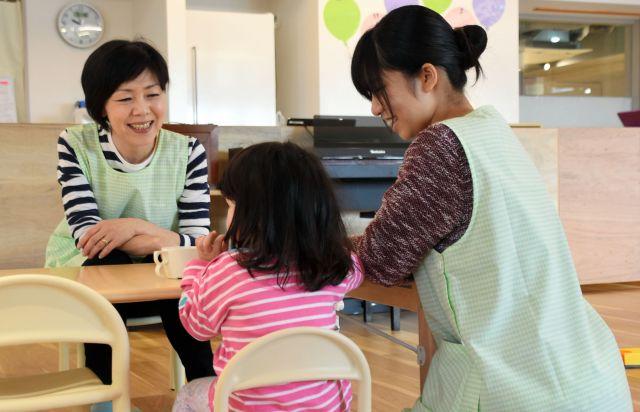 マンション内の保育園で、おやつを食べる子どもを見守る保育士=千葉県柏市